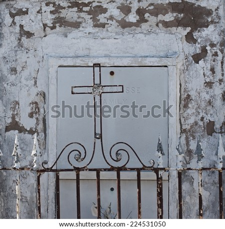 wrought iron cross in front of grey tomb background - stock photo