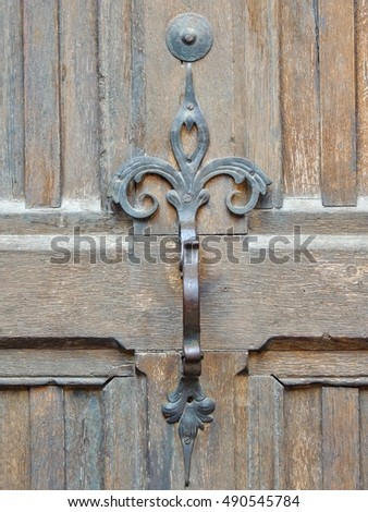 Wrought iron door pull handle decorating an antique front entry