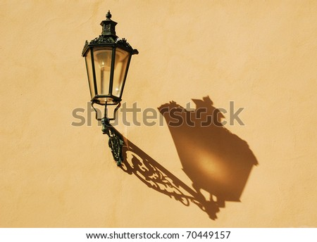 Wrought-iron lantern with its shadow on the yellow wall, Prague, Czech Republic