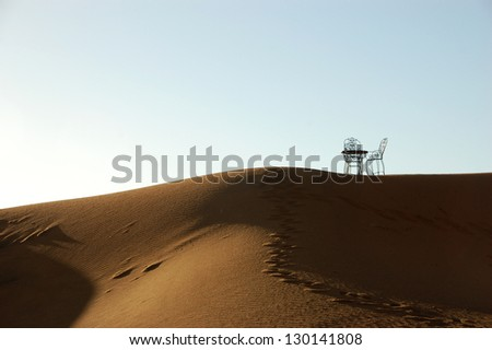 Wrought iron table and chairs on the top of sand dune of Erg Chebbi in the Sahara Desert, Morocco