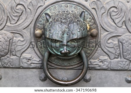 Wrought iron vintage door knocker - knob in the form of a cat head - stock photo