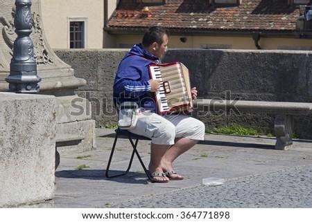 Wurzburg, Germany - May 4, 2014: Man playing the accordeon on the old Main Bridge below Marienburg Castle in Wurzburg, Germany on May 4, 2014 - stock photo