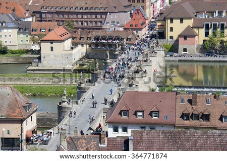 Wurzburg, Germany - May 4, 2014: People cross the old Main Bridge across the Main river seen from above in Wurzburg, Germany on May 4, 2014 - stock photo