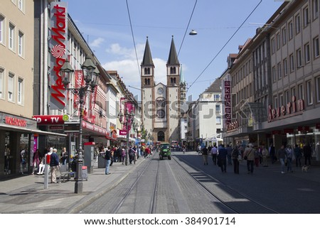 Wurzburg, Germany - May 4, 2014: People walk in a shopping street in front of the Wurzburger Dom church in central Wurzburg, Germany on May 4, 2014