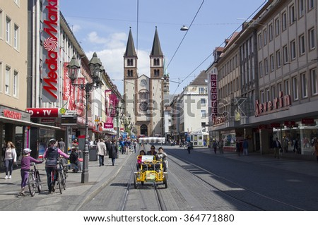 Wurzburg, Germany - May 4, 2014: Walking people and a mother and children in a four wheel yellow city bicycle in a street leading to the Wurzburger Dom church in Wurzburg, Germany on May 4, 2014 - stock photo
