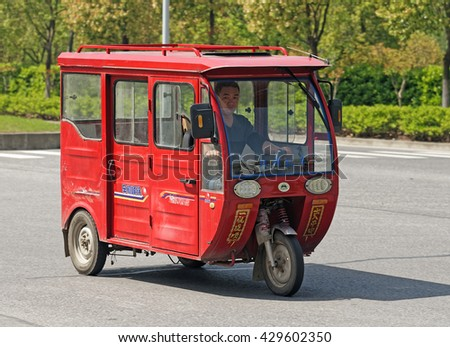 WUXI, CHINA - April 18, 2016: Auto rickshaw in Wuxi. Auto rickshaws are very popular in China as an alternative to cars because of their low cost. - stock photo