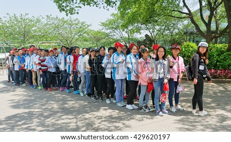 WUXI, CHINA - April 18, 2016: Group of students at Turtle Head Park in Wuxi. Turtle Head Park is the cityâ??s most attractive park and best place to admire the beauty of this lake.