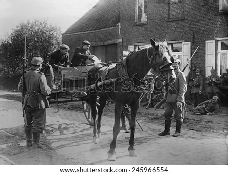 WWI. Belgian peasants in a horse-drawn cart, showing a pass to soldiers during the WWI German occupation of Belgium. 1914-15.