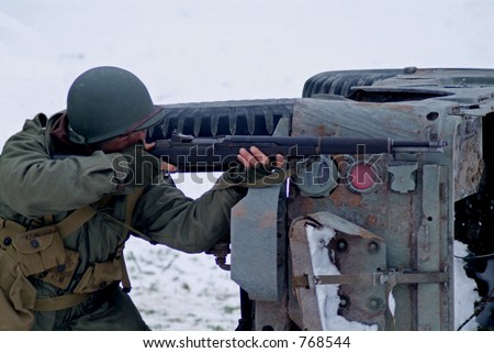WWII Soldier in a winter setting. (firing a rifle) - stock photo