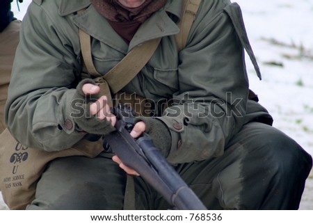WWII Soldier in a winter setting. (reloading a rifle) - stock photo