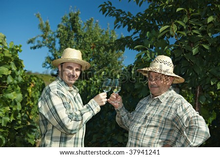 WWinemakers celebrating vintage outdoors in vinery. - stock photo