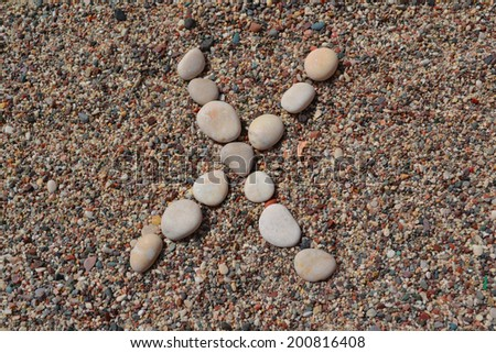 X letter made of stones on sand - stock photo