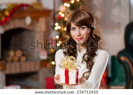 x-mas, winter, happiness, holidays and people concept - smiling woman with small gift box over living room and christmas tree background - stock photo