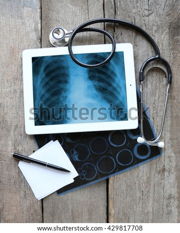 X-ray on the tablet screen with stethoscope on wooden background - stock photo