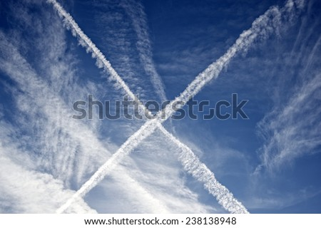 X shape created in the sky by passing by planes with some other clouds, makes a great nature background - stock photo