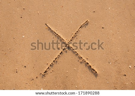 X text written in the sandy on the beach - stock photo