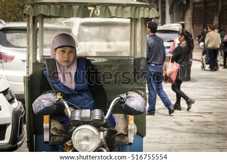 XIAN, CHINA - April 8, 2016: Chinese female moto-rickshaw driver waiting for the clients on one of the streets in Muslim area of Xian, China on April 8, 2016