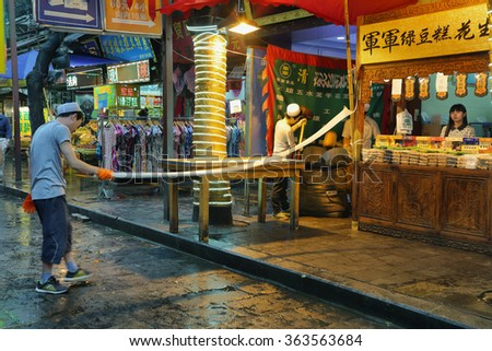 XIAN, CHINA - SEPTEMBER 9, 2015: unidentified man making handmade pasta in a food store on a rainy day in the Muslim Quarter of Xian, China. - stock photo
