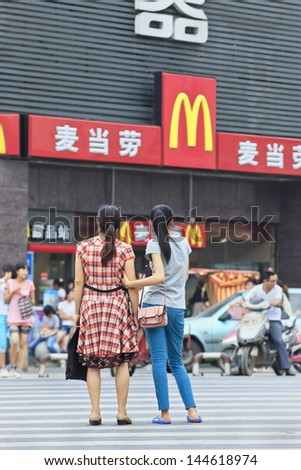 XIANG YANG-CHINA-JULY 3. Mom and daughter in front of McDonald. It took the fast food giant 19 years to reach 1,000 restaurants in China. It plans to have 2,000 by 2013. Xiang Yang, July 3, 2012. - stock photo
