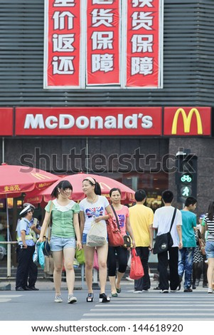 XIANG YANG-CHINA-JULY 3. Pedestrians in front of McDonald outlet. It took McDonald 19 years to reach 1,000 restaurants in China, It plans to double it to 2,000 at this year.  Xiang Yang, July 3, 2012 - stock photo