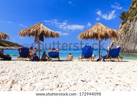 XIGIA, GREECE - JULY 2013: People are relaxing under a straw parasol on the beach at Xigia on the island of Zakynthos in July 2013