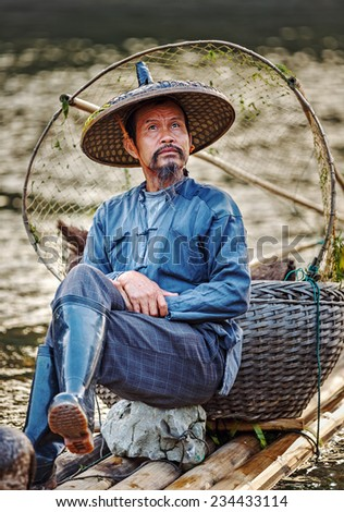 XINGPING, CHINA - OCTOBER 22, 2014: Cormorant fisherman sits on the ancient bamboo boat before fishing - The Li River, Xingping, China - stock photo