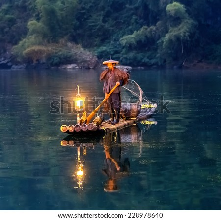 XINGPING, CHINA - OCTOBER 21, 2014: Cormorant fisherman stands on the ancient bamboo boat in the sunrise - The Li River, Xingping, China - stock photo
