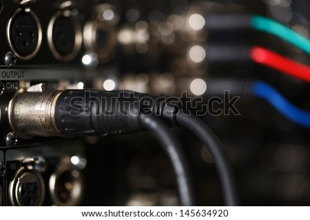 XLR audio digital cables in the rear panel of the professional VCR. RGB video cables in blur. - stock photo