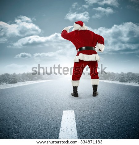 xmas background of winter road and old big red santa claus and sun light