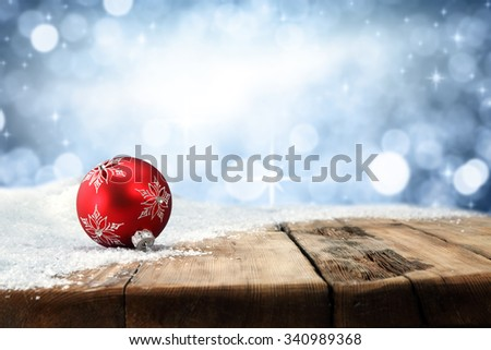 xmas blue wall wooden retro table snow and red ball place  - stock photo