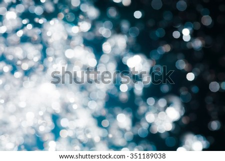 Xmas blurred wallpaper of falling snow. Spots of light bokeh. Defocused abstract blue christmas background.  - stock photo