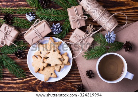 Xmas holiday background with homemade christmas cookies, cup of coffee,  blank card for holiday message, spruce twigs and gift boxes, top view, selective focus - stock photo