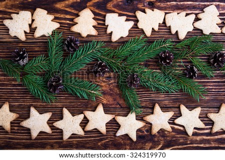 Xmas holiday background with spruce twigs, christmas tree and star shaped cookies, top view, selective focus - stock photo