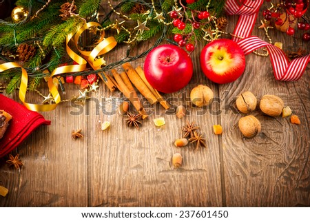 Xmas holiday table setting border design, decorated with garlands, baubles, walnuts, hazelnuts, cinnamon sticks. Warm colors toned. Christmas Traditional Sweets - stock photo
