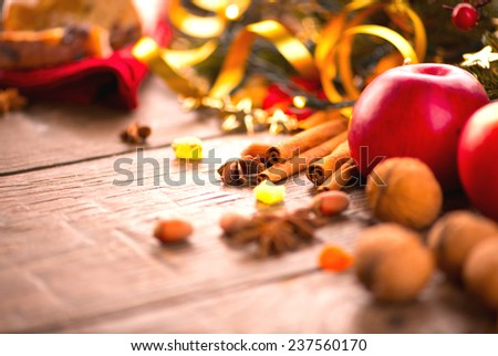 Xmas holiday table setting, decorated with garlands, baubles, wallnuts, hazelnuts, cinnamon sticks. Warm colors toned. Traditional  Christmas sweets food. Vintage style toned image  - stock photo