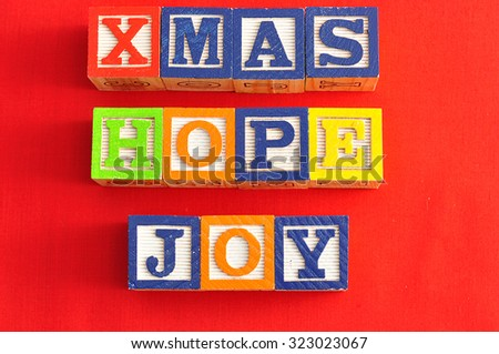 Xmas, Joy and Hope spelled with Alphabet blocks on a red background
