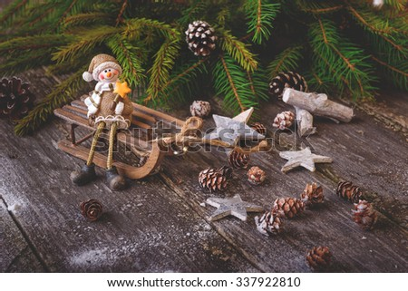 Xmas or new year composition with holiday decoration - sledge, little man figures and fir branches, pinecones on wooden background. Xmas card. Space for text. Instagram colors toning. Vintage style - stock photo