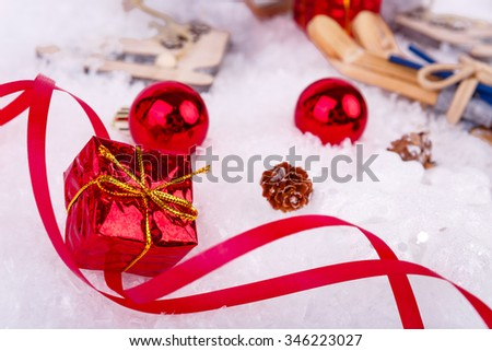 Xmas or new year composition with holiday decorations - little cristmas baubles, red satin ribbon on snow with toy skates, skis and little gift. Christmas card