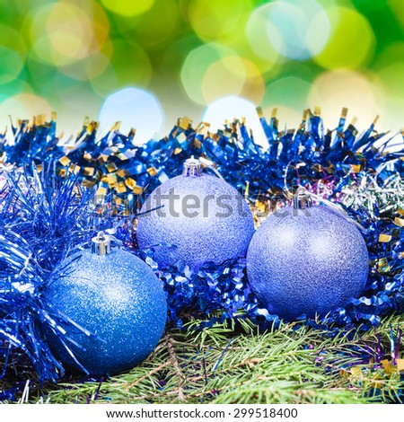Xmas still life - blue balls, tinsel at green tree with blurred green Christmas lights background - stock photo