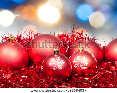 Xmas still life - red balls, tinsel with diffuse blue Christmas lights background