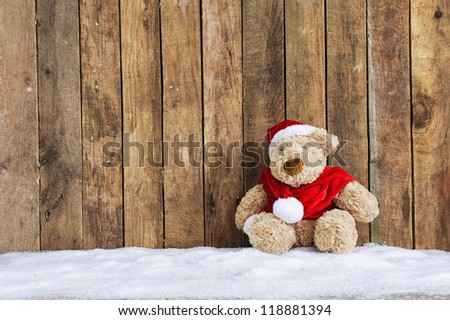 xmas teddy bear sitting in the snow - stock photo