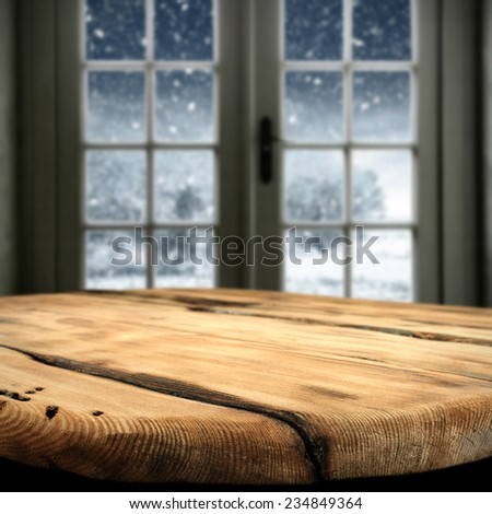 xmas window and worn old table of christmas time  - stock photo
