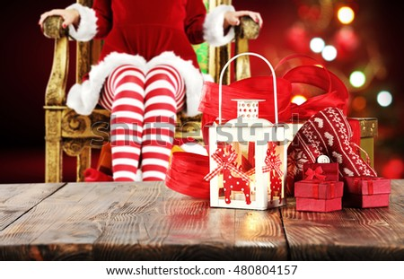 xmas wooden old table place and free space for your decoration with background of woman legs and xmas tree