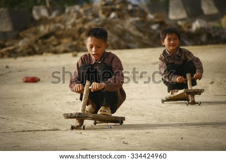 Y Ty, Lao Cai province, Viet Nam - Sept 27, 2015 - Children playing with homemade wooden car in northern Vietnam highlands near the Chinese border.