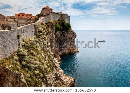 Yacht and Impregnable Walls of Dubrovnik, Croatia - stock photo