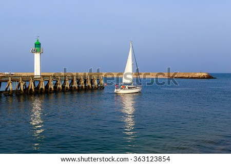 Yacht and lighthouse in the city of Deauville, Normandy, France - stock photo