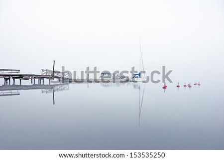 Yacht and other boats moored at jetty in heavy morning fog - stock photo