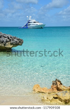 Yacht at anchor near beach with giant water slide - stock photo