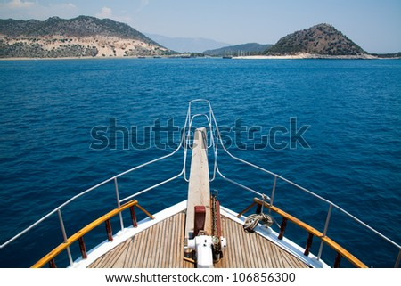 Yacht at sea with the mountains in the background