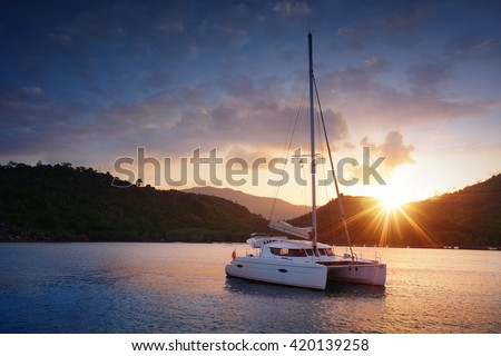 Yacht - Catamaran in the tropical sea at sunset. Yachting theme. Yachting background. Sailing time. Sailboat. Yacht. Luxury yacht. - stock photo